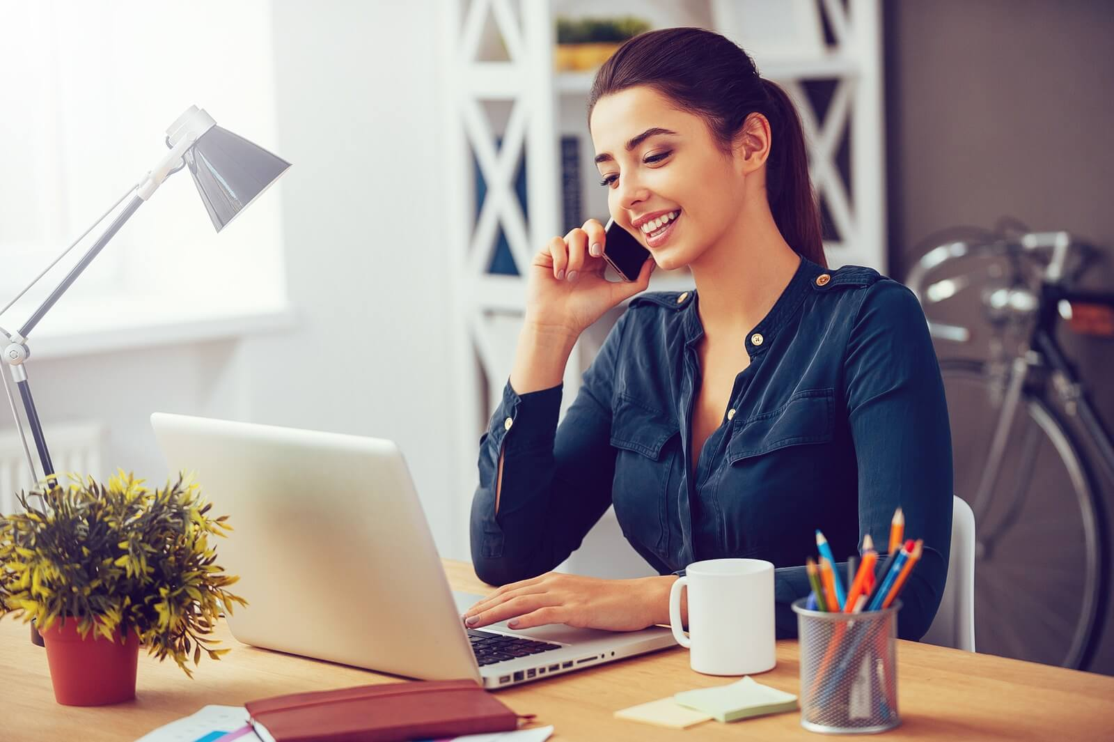 smiling woman talking on the phone in her home office